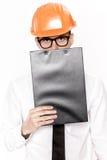 Портрет молодого инженера по строительству и монтажу в оранжевом шлеме с папкой на белой предпосылке Стоковая Фотография