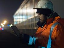 Портрет молодого инженера работая на таблетке во время otdoors hignt в шлеме и отражательной куртке Стоковая Фотография RF