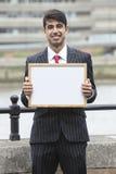 Портрет молодого индийского бизнесмена держа пустой знак Стоковые Изображения