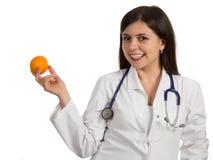 Портрет молодого красивого женского доктора держа апельсин Стоковые Фотографии RF