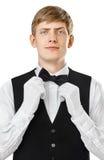 Портрет молодого красивого кельнера исправляя его бабочка на костюме Стоковое Изображение