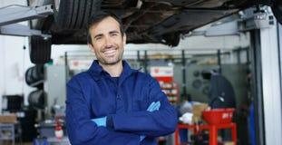 Портрет молодого красивого механика автомобиля в мастерской автомобиля, на заднем плане обслуживания Концепция: ремонт машин, dia Стоковые Фотографии RF