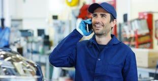 Портрет молодого красивого механика автомобиля в мастерской автомобиля, на заднем плане ремонта концепции обслуживания автомобиля Стоковые Фото