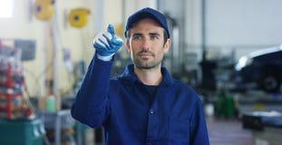 Портрет молодого красивого механика автомобиля в мастерской автомобиля, на заднем плане обслуживания Концепция: ремонт машин, dia Стоковые Изображения