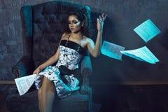 Портрет молодого красивого музыканта девушки сидя на кресле бархата сером и бросая нотах прочь Стоковое Изображение