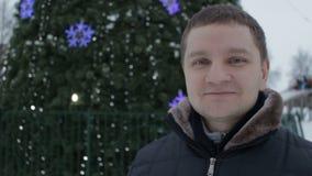 Портрет молодого красивого усмехаясь человека внешнего, рождественской елки в парке зимы сток-видео