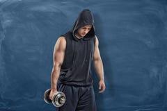 Портрет молодого красивого человека в черном обмундировании стоя и держа серебряная гантель в его руке во время тренировки Стоковые Изображения