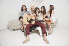 Портрет молодого мужского гитариста сидя между молодыми женскими друзьями Стоковые Изображения RF