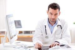 Портрет молодого доктора анализируя рентгенографирование Стоковая Фотография