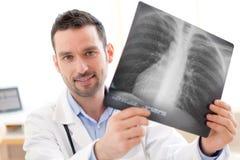 Портрет молодого доктора анализируя рентгенографирование Стоковое Изображение
