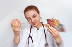 Портрет молодого доктора с яблоком и пилюлек в руках Стоковые Фотографии RF