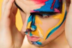 Портрет молодого привлекательного человека с покрашенной краской стороны на желтой предпосылке Профессиональная мода состава ffan Стоковые Фотографии RF