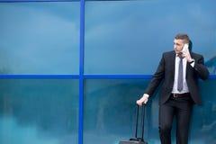 Портрет молодого путешественника в костюме стоя с чемоданом и мамами стоковые фотографии rf