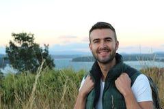 Портрет молодого туриста в одеждах и рюкзаке горы стоя на верхней части горы и наслаждаясь взглядом ландшафта пейзажа стоковое фото rf