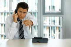 портрет молодого уверенно кавказского бизнесмена говоря на телефоне Стоковые Изображения