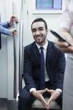 Портрет молодого усмехаясь бизнесмена сидя на метро и смотря камеру Стоковые Фотографии RF