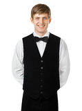 Портрет молодого усмехаясь кельнера стоя с руками за его Стоковое Изображение