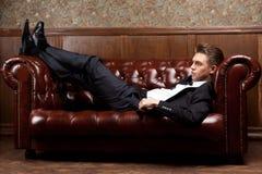 Портрет молодого человека лежа на кожаной софе Стоковое фото RF