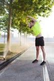 Портрет молодого человека играя спорт на вымощенной дороге в пасмурном утре пока слушающ к музыке в наушниках на его черни Стоковое Изображение RF