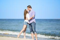 Портрет молодого человека и женщины целуя на пляже Стоковое Фото