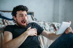 Портрет молодого человека ослабляя и смотря тв-шоу на планшете стоковые фотографии rf