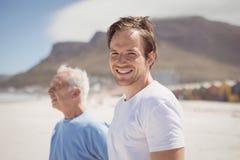 Портрет молодого человека при его отец стоя на пляже Стоковое Изображение