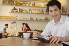 Портрет молодого человека работая на кофейне Стоковые Изображения