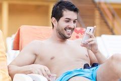 Портрет молодого человека смеясь над с телефоном в руках Стоковая Фотография RF