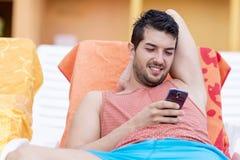 Портрет молодого человека смеясь над с телефоном в руках Стоковое Изображение