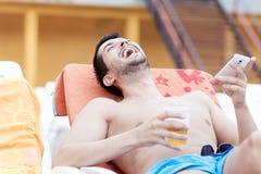Портрет молодого человека смеясь над с телефоном в руках Стоковые Изображения RF