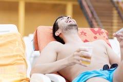 Портрет молодого человека смеясь над с телефоном в руках Стоковое фото RF