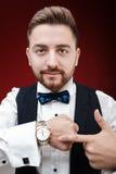 Портрет молодого человека с бородой показывает к вахте на темном backgro Стоковая Фотография