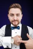 Портрет молодого человека с бородой показывает к вахте на темном backgro Стоковые Изображения RF