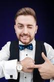 Портрет молодого человека с бородой показывает к вахте на темном backgro Стоковое Изображение RF