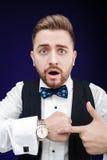 Портрет молодого человека с бородой показывает к вахте на темном backgro Стоковая Фотография RF