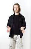 Портрет молодого человека с длинными светлыми волосами, черной рубашкой, белым b Стоковая Фотография