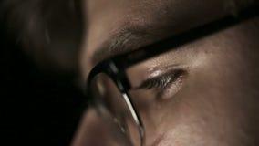 Портрет молодого человека с стеклами который работает на ноче конец вверх сток-видео
