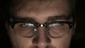 Портрет молодого человека с стеклами который работает на ноче конец вверх видеоматериал