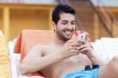 Портрет молодого человека усмехаясь с телефоном в руках Стоковое Фото