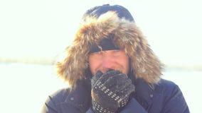 Портрет молодого человека outdoors замерзая смотреть в камеру в дне зимы солнечном конец вверх Стоковые Фотографии RF