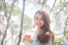 Портрет молодой азиатской женщины выпивая ее чай утра Упал r Стоковое Фото