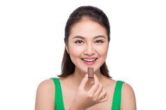 Портрет молодой азиатской женщины держа шоколадный батончик для того чтобы насладиться Стоковые Изображения RF