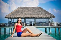 Портрет молодой азиатской смотря женщины сидя около ресторана на красивом тропическом пляже на Мальдивах Стоковое Фото