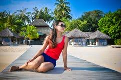 Портрет молодой азиатской смотря женщины сидя около ресторана на красивом тропическом пляже на Мальдивах Стоковые Фотографии RF
