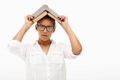 Портрет молодой африканской девушки с книгой над белой предпосылкой Стоковое Фото