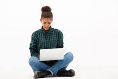 Портрет молодой африканской девушки с компьтер-книжкой над белой предпосылкой Стоковое Изображение
