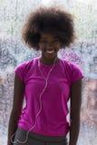 Портрет молодой афро американской женщины в спортзале пока слушая mus Стоковые Изображения