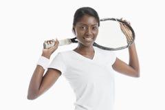 Портрет молодой Афро-американской женщины держа ракетку над белой предпосылкой стоковое изображение