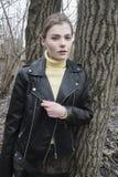 Портрет молодой белокурой женщины в черной куртке в древесинах Стоковые Фото