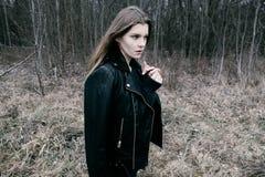 Портрет молодой белокурой женщины в черной куртке в древесинах Стоковая Фотография